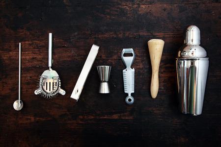 cocteles: Conjunto de bar o pub accesorios con una coctelera de martini dispuestos en una l�nea ordenada sobre un fondo negro
