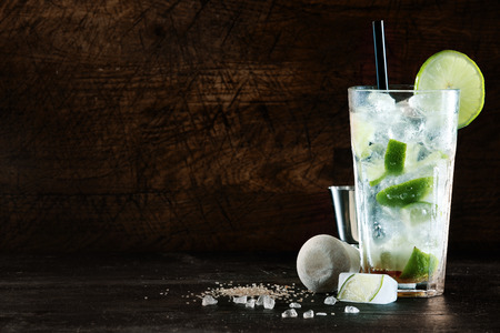 Rafraîchissant cocktail de Noël avec un mélange d'alcools blancs, mixer et d'herbes aromatiques fraîches dans un grand verre avec de la glace garnie de citron acidulé, fond sombre avec copyspace Banque d'images - 31443593