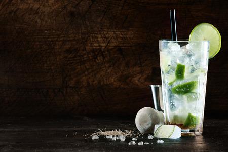 Verfrissende Kerstmis cocktail met een mix van terpentine, mixer en verse aromatische kruiden in een hoog glas met ijs gegarneerd met pittige citroen, donkere achtergrond met copyspace