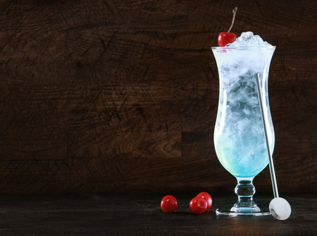 Elegant blue curacao cocktail with ice and a swizzle-stick garnished with fresh cherries on a dark background with copyspace for your Christmas message or tropical vacation text 版權商用圖片