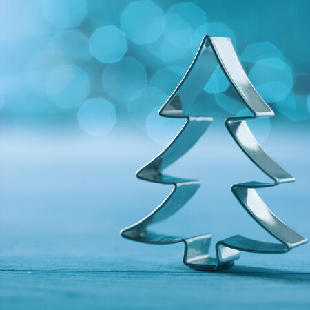 Shiny silver cookie cutter Christmas tree decoration on a wintry cold blue background with a bokeh of twinkling party lights and copyspace , square format photo