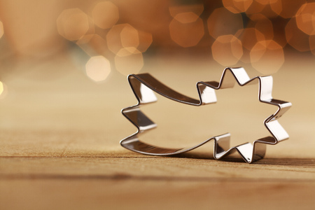 Decorative shiny metallic shooting star Christmas cookie cutter against a sepia colored background with a bokeh of twinkling party lights and copyspace for your Xmas or Advent greeting photo