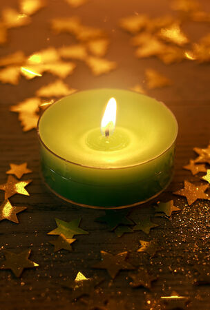 Green Christmas candle burning with glowing light surrounded by small golden decorative star shapes, high-angle close-up photo