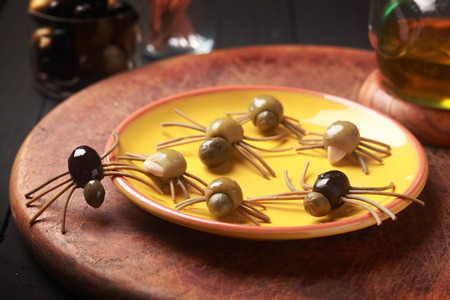 grisly: Creepy crawly edible Halloween spiders made from cured green and black olives with Italian spaghetti legs on a side table at a Halloween party for appetizers or favors for trick-ot-treating