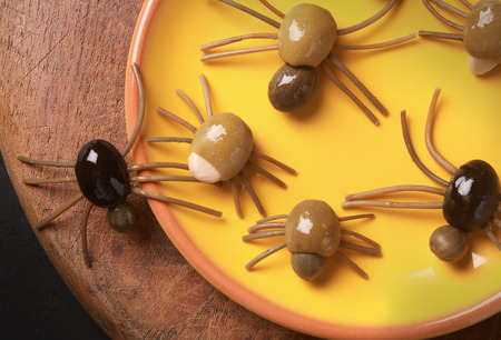 grisly: Cute spooky Halloween spider appetizers made from green, black and stuffed olives with spaghetti legs crawling off a yellow platter onto a wooden table, view from above Stock Photo