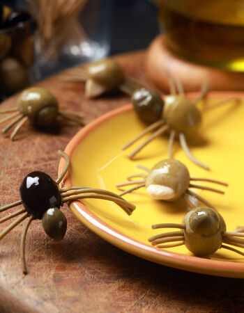 grisly: Scary creepy Halloween spider snacks served at a festive party made from cured green and black olives with pasta legs crawling all over the table from a yellow plate