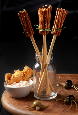 broomsticks: Creative Halloween snacks and appetizers with witches broomsticks made from bread sticks and pretzels with creepy spiders of olives and spaghetti on a table at a Halloween celebration Stock Photo
