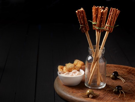 broomsticks: Witches broomsticks at a Halloween party made from bread sticks and pretzels standing in a glass jar on a table decorated with creepy spiders made from olives and spaghetti