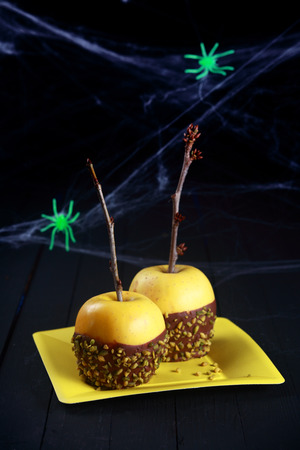 festooned: Creepy Halloween dessert of dipped chocolate apples festooned in spider webs with green spiders served on a yellow platter