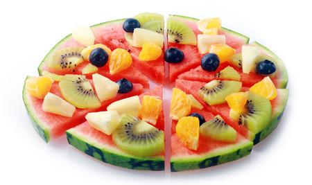 トロピカル フルーツ、パイナップル、オレンジ、キウイ フルーツ、健康的なベジタリアン料理の白い背景の上のセグメントにカット ブルーベリー 写真素材