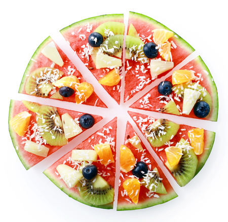 Colorful tropical fruit watermelon pizza topped with kiwifruit, blueberries, orange, pineapple, and sprinkled with desiccated coconut, cut into segments for serving, on white overhead view photo