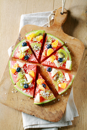 Overhead view of a colorful tropical fruit watermelon pizza topped with kiwifruit, blueberries, orange, pineapple, and sprinkled with desiccated coconut cut into segments on a rustic wooden board