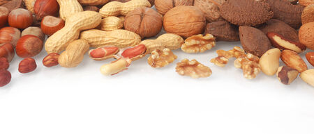 Mixed whole and shelled nuts in a horizontal banner including hazelnuts, brazil nuts, peanuts or groundnuts and walnuts on white with copyspace below photo