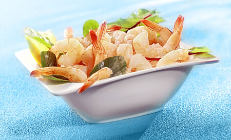 Bowl of delicious grilled prawn or shrimp tails garnished with fresh lemon and baby spinach on a colorful turquoise blue background photo