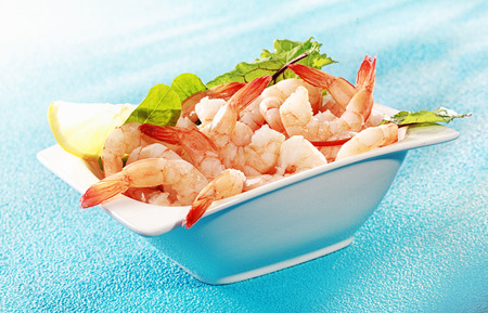 Delicious seafood appetizer of grilled shrimp or pink prawns served in a dish with a slice of lemon and salad greens on a turquoise blue background photo