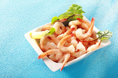 Gourmet pink prawn or shrimp tails served in a dish with lemon and fresh herbs for a delicious seafood appetizer to a dinner, high angle view on turquoise blue with copyspace photo