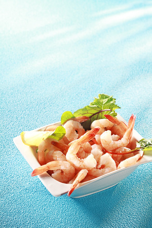 Fresh pink prawn or shrimp appetizer served with sliced lemon and leafy greens for a gourmet shellfish start to a meal, on blue with copyspace photo