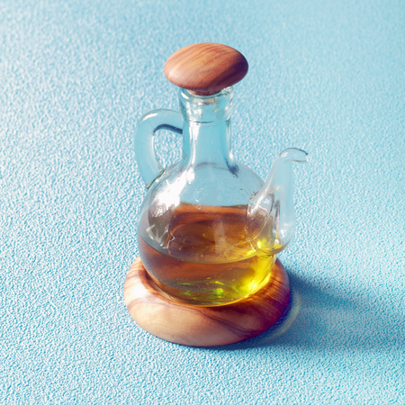 Clear glass decanter of golden virgin olive oil on a wooden stand for serving as a salad dressing or to use as an ingredient in cooking, on blue photo