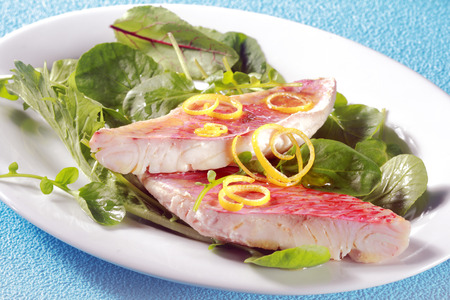 ovenbaked: Grilled fresh fish fillets garnished with lemon zest on leafy green salad with herbs and baby spinach for a tasty seafood meal or appetizer Stock Photo