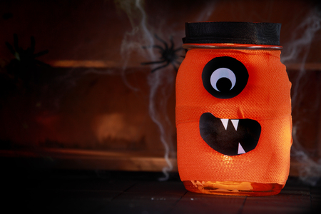 festooned: Orange jar decorated as a Halloween monster with a scary Cyclops face standing on rustic wooden shelves festooned in spiders and cobwebs on a shadowy background with copyspace