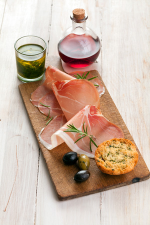 Thinly sliced gourmet Italian prosciutto ham with cured olives and golden toasted herb bread on a wooden board on a rustic white table photo