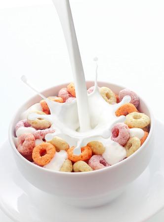 Pouring fresh creamy milk into a bowl of colorful fruit loops breakfast cereal in a white ceramic bowl with a splash on a white background with copyspace photo