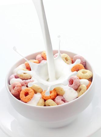 gaza: Verter la leche cremosa fresca en un tazón de frutas de colores bucles cereal para el desayuno en un tazón de cerámica blanca con un chapoteo en un fondo blanco con copyspace Foto de archivo