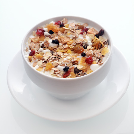 Bowl of delicious breakfast muesli with oat and wheat flakes mixed with dried fruit and nuts served in a white ceramic bowl for a healthy nutritious meal
