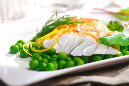 맛있는 오븐 구이 물고기 또는 구운 필렛 또는 스테이크와 완두콩, mangetout 포드, 레몬 향 및 영양가있는 해산물 저녁 식사를위한 신선한 딜