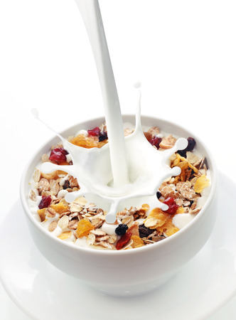 Milk splashing into a bowl of fresh muesli with a mix of wheat, oats and bran with dried fruit and nuts over white with copyspace 스톡 콘텐츠