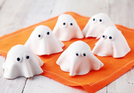 trick or treating: Scary white edible Halloween ghost appetizers for party snacks or treats for young children trick-or-treating on Allhallows Eve standing ready on a colorful orange napkin