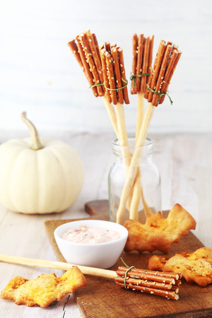 broomsticks: Rustic appetizers for a Halloween party with Witches broomsticks made from bread sticks and pretzels and bat cookies or biscuits served with a savory dip with a white autumn pumpkin behind