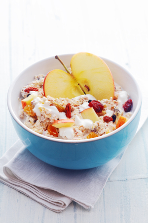 Bowl of healthy breakfast cereal with a halved fresh apple and topped with diced apple, dried fruit and nuts served with milk in a blue ceramic bowl photo