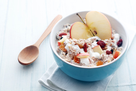 Healthy bowl of muesli, apple, fruit, nuts and milk