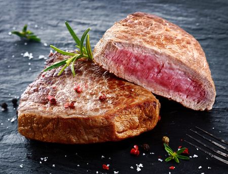 Two portions of lean trimmed grilled beef steak cut through to show the succulent tender red meat and seasoned with rosemary, salt and pepper in a steakhouse or restaurant photo