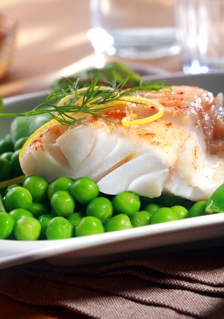 ovenbaked: Delicious seafood meal of grilled or oven-baked fish fillet served with juicy green petit pois peas , lemon zest and dill at a restaurant