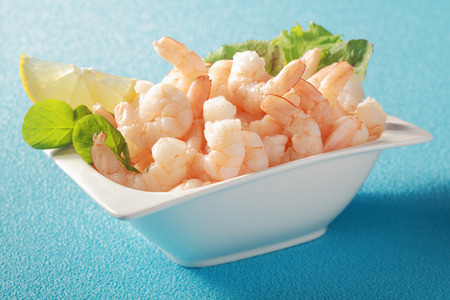 Grilled shelled pink prawns served in a white dish with fresh leafy green herbs as a gourmet appetizer to a dinner, on a blue table photo
