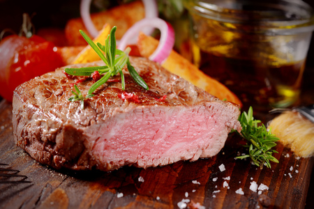 fillet steak: Succulent tender rare beef steak grilled to perfection sliced through to show the texture seasoned with fresh rosemary and salt