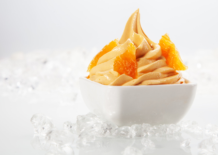 frozen joghurt: Close Delicious Yellow Frozen with Tasty Toppings on White Bowl Surrounded by Ice. Served on White Table. Stock Photo