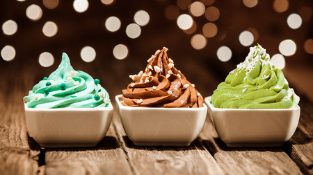 Colorful row of three different frozen yogurt desserts in blue, brown and green garnished with nuts and sugar pearls at a party with a sparkling background bokeh of lights Stock Photo