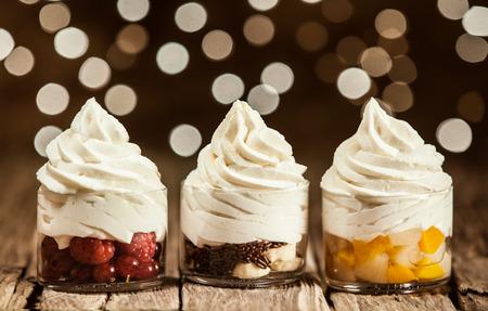 Yummy Frozen yoghurt op ronde glazen containers met diverse vruchten Geplaatst op houten tafel.