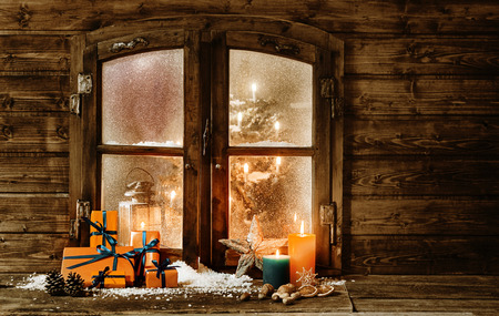 Festive wooden Christmas cabin window with gift-wrapped colorful orange presents, burning candles and decorations in winter snow and a glimpse of a decorated Christmas tree through the frosted window