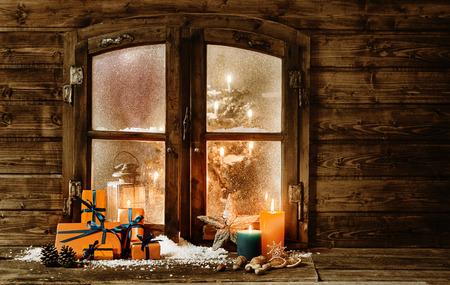 caba�a: Ventana de la cabina de madera festiva de Navidad con los presentes regalo-envueltos de colores naranja, velas encendidas y adornos en la nieve del invierno y una visi�n de un �rbol de Navidad decorado a trav�s de la ventana de vidrio esmerilado Foto de archivo