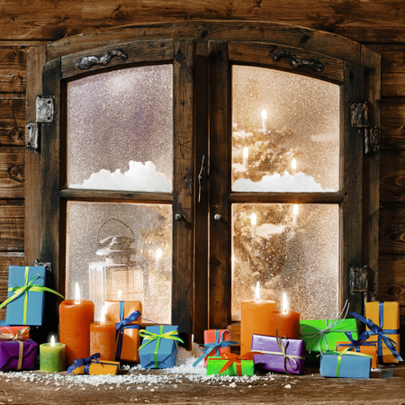 Colorful Christmas gifts and glowing multicolored candles on a windowsill of a rustic timber cabin with a view through the snowy frosted window of a decorated Xmas tree