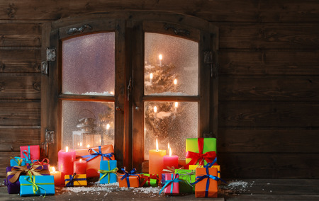 Plenty Colored Gift Boxes and Lighted Candles at Window Pane on Christmas Season.