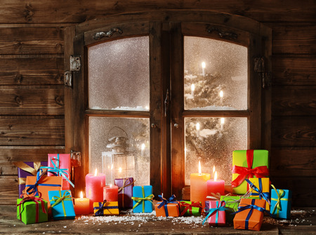 bow window: Various Colored Christmas Presents and Lighted Candles at Vintage Window Pane