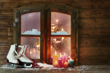 White Ice Skates and Assorted Color Lighted Candles at Snowy Wooden Window Pane on Christmas Season.