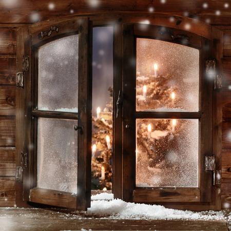Cierre de nieve en madera del vintage Navidad del cristal de ventana, Capturado con árbol de Navidad y luces en el interior. Foto de archivo