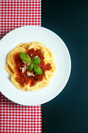 bolognaise: Plate of spaghetti Bolognaise or Bolognese with a rich tomato and ground beef sauce garnished with basil and parmesan cheese