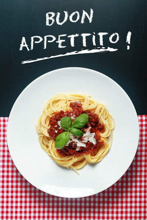 buon: Overhead view of a plate of spaghetti Bolognaise or Bolognese under a Buon Appetito handwritten sign with a rich tomato and ground beef sauce garnished with basil and parmesan cheese Stock Photo